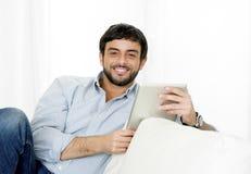 Gelukkige Jonge aantrekkelijke Spaanse mens thuis op witte laag die digitaal tablet of stootkussen gebruiken Stock Afbeelding