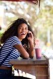 Gelukkige jonge africana Amerikaanse vrouw die en op mobiele telefoon bij koffie lachen spreken Royalty-vrije Stock Foto's