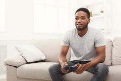 Gelukkige jonge Afrikaans-Amerikaanse mens die thuis videospelletjes spelen stock fotografie