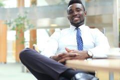 Gelukkige jonge Afrikaans-Amerikaanse zakenman die camera bij werkplaats in bureau bekijken stock foto's