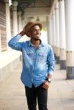Gelukkige jonge Afrikaanse Amerikaanse mens die met hoed lopen Royalty-vrije Stock Foto