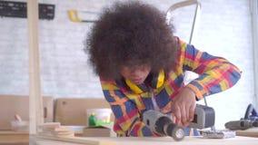 Gelukkige jonge Afrikaanse Amerikaanse vrouw met Afro-kapsel die reparaties, houtbewerking doen stock video