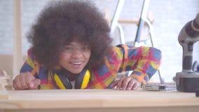 Gelukkige jonge Afrikaanse Amerikaanse vrouw met Afro-kapsel tevreden met haar werk, blaast zij het schaafsel weg stock video