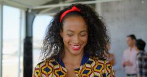 Gelukkige jonge Afrikaanse Amerikaanse vrouwelijke directeur die zich in modern bureau 4k bevinden stock videobeelden