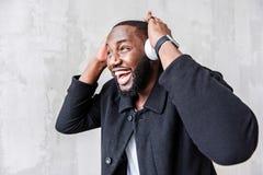 Gelukkige jonge Afrikaanse kerel die aan muziek via slimme telefoon luisteren stock afbeelding
