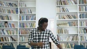 Gelukkige jonge Afrikaanse mens het luisteren muziek in de hoofdtelefoon en het dansen in de bibliotheek stock footage