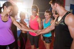 Gelukkige jonge atleten die handen stapelen tegen boksring stock fotografie