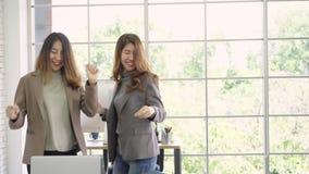 Gelukkige jonge Aziatische vrouw die kostuum dragen die terwijl het werken in haar bureau dansen De mooie tiener geniet van en he stock video