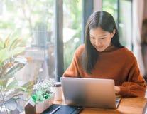 Gelukkige jonge Aziatische vrouw die met laptop zij werken die het scherm bekijken stock foto