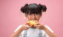 Gelukkige jonge Aziatische vrouw die plak van pizza eten royalty-vrije stock afbeeldingen