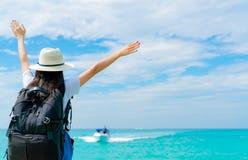 Gelukkige jonge Aziatische vrouw op toevallige stijlmanier met strohoed en rugzak Ontspan en geniet van vakantie bij tropisch par royalty-vrije stock fotografie