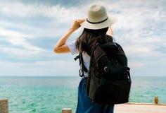 Gelukkige jonge Aziatische vrouw op toevallige stijlmanier met strohoed en rugzak Ontspan en geniet van vakantie bij tropisch par royalty-vrije stock foto's