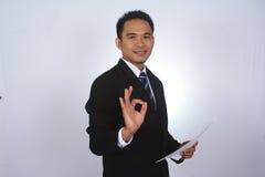 Gelukkige jonge Aziatische zakenman met document en het tonen van o.k. die teken op wit wordt geïsoleerd Royalty-vrije Stock Afbeelding