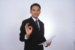 Gelukkige jonge Aziatische zakenman met document en het tonen van o.k. teken Stock Foto's