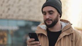 Gelukkige jonge baardmens die smartphone in de straat gebruiken dichtbij winkelcomplex Hij draagt een de herfstjasje en een gebre stock videobeelden