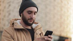 Gelukkige jonge baardmens die smartphone in de straat gebruiken dichtbij winkelcomplex Hij draagt een de herfstjasje en een gebre stock video