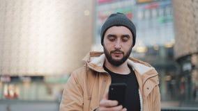 Gelukkige jonge baardmens die smartphone gebruiken die in de straat dichtbij winkelcomplex lopen Hij draagt een de herfstjasje en stock video