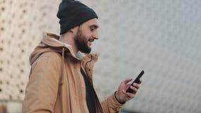 Gelukkige jonge baardmens die smartphone gebruiken die in de straat dichtbij winkelcomplex lopen Hij draagt een de herfstjasje en stock footage