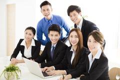Gelukkige jonge bedrijfsmensen die in bureau werken stock afbeelding