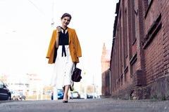 Gelukkige jonge bedrijfsvrouw die op de straat lopen stock foto's