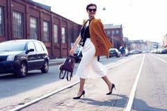 Gelukkige jonge bedrijfsvrouw die op de straat lopen royalty-vrije stock afbeeldingen