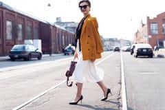 Gelukkige jonge bedrijfsvrouw die op de straat lopen stock fotografie
