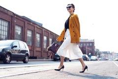 Gelukkige jonge bedrijfsvrouw die op de straat lopen royalty-vrije stock afbeelding