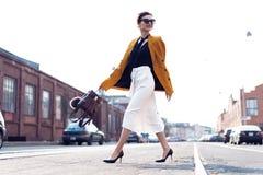 Gelukkige jonge bedrijfsvrouw die op de straat lopen stock foto