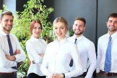 Gelukkige jonge bedrijfsvrouw die zich voor haar team bevinden royalty-vrije stock foto