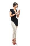Gelukkige jonge bedrijfsvrouw in formeel kostuum die en op de mobiele telefoon ontspannen typen royalty-vrije stock afbeelding