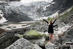 Gelukkige jonge blonde vrouw in zwarte kleding onder de reusachtige stenen op de gletsjer Mestia stock afbeelding