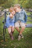 Gelukkige Jonge Broer en Zuster Sitting Together Outside Stock Afbeelding