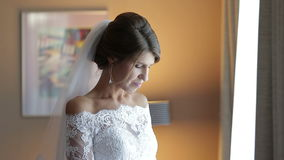 Gelukkige jonge bruid die op de bruidegom bij het venster wachten stock footage