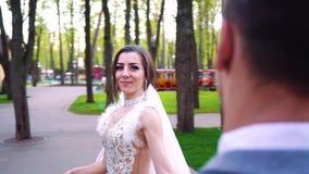 Gelukkige jonge bruid die rond bruidegom lopen die zich nog in zonnig park bevinden stock video
