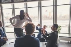 Gelukkige jonge businesswomans en businessmans het doen van hoogte vijf in bureau Royalty-vrije Stock Afbeeldingen