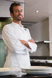 Gelukkige jonge chef-kok die zich met die wapens bevinden achter teller worden gekruist Stock Fotografie