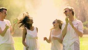 Gelukkige jonge dansende vrienden die poederverf bespuiten bij muziekfestival, Holi stock video