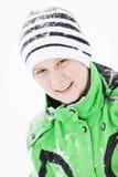 Gelukkige jonge die jongen met de wintersneeuw wordt bestrooid Stock Afbeeldingen