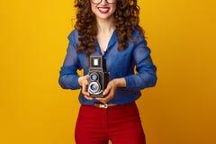 Gelukkige jonge die vrouw op geel met retro fotocamera wordt geïsoleerd Stock Afbeelding