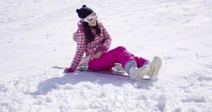 Gelukkige jonge die vrouw op snowboard wordt gezeten stock video