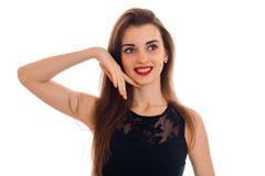 Gelukkige jonge donkerbruine dame met rode weg en lippen en zwarte kleding die geïsoleerd op witte achtergrond eruit zien glimlac Royalty-vrije Stock Fotografie