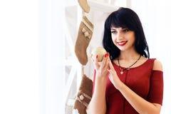 Gelukkige jonge donkerbruine vrouw die in rode kleding een Kerstmisbal houden Stock Foto's