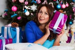 Gelukkige jonge donkerbruine vrouw het openen giftdoos dichtbij Kerstmisboom Royalty-vrije Stock Fotografie