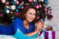 Gelukkige jonge donkerbruine vrouw het openen giftdoos dichtbij Kerstmisboom Royalty-vrije Stock Afbeelding