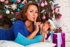 Gelukkige jonge donkerbruine vrouw het openen giftdoos dichtbij Kerstmisboom Royalty-vrije Stock Afbeeldingen