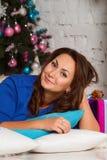 Gelukkige jonge donkerbruine vrouw het openen giftdoos dichtbij Kerstmisboom Stock Foto's