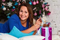 Gelukkige jonge donkerbruine vrouw het openen giftdoos dichtbij Kerstmisboom Stock Afbeelding