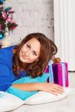 Gelukkige jonge donkerbruine vrouw met giftdoos dichtbij Kerstmisboom X Royalty-vrije Stock Afbeelding