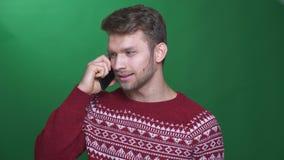 Gelukkige jonge donkerbruine zakenman die op cellphone spreken die blij en blij op groene achtergrond zijn stock video