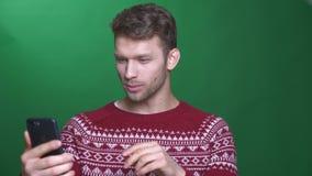 Gelukkige jonge donkerbruine zakenman die in videochat die op cellphone spreken blij en aandachtig op groene achtergrond zijn stock videobeelden